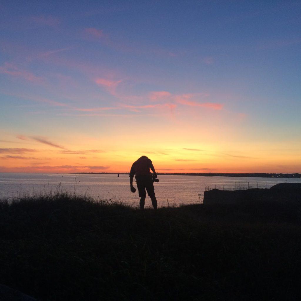 Homme à contre-jour sur la soute devant la rade de Lorient